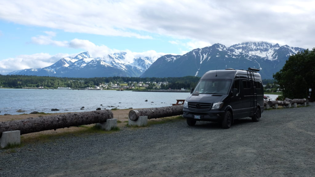 so we bought a van parked in front of alaska mountain range in haines