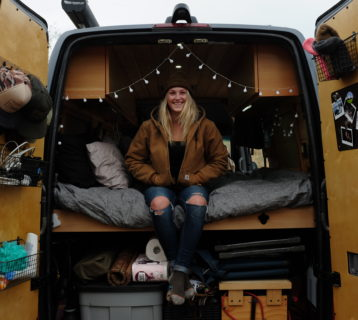 katie from so we bought a van sitting on bed with rear doors open