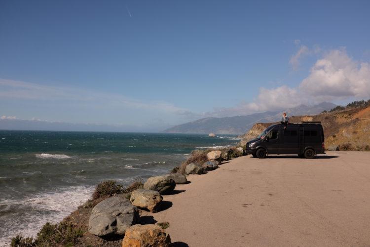 Katie sitting on the van overlooking the ocean in big sur california